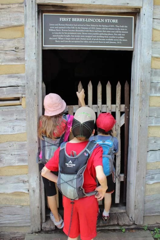 Three kids peering into a building.