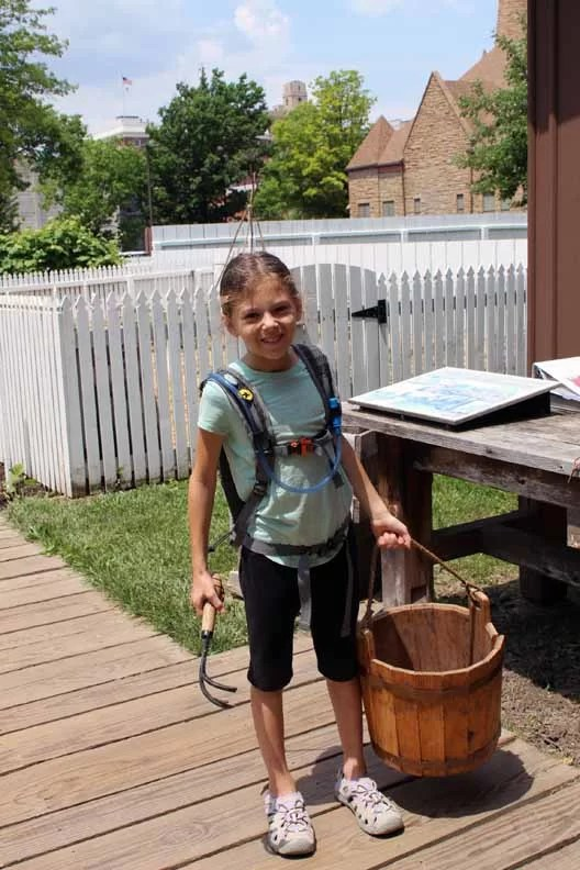 A little girl holding an old bucket and yard tool.