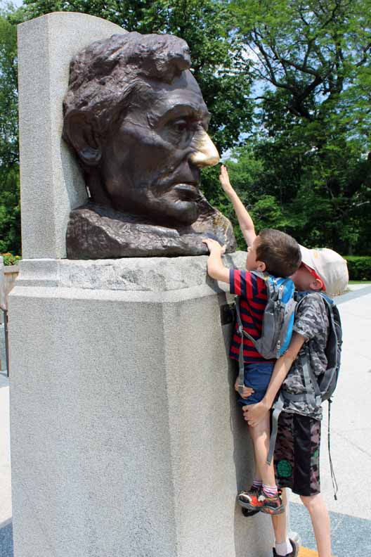 A kid getting help from his brother to rub the nose of Lincoln on a statue.
