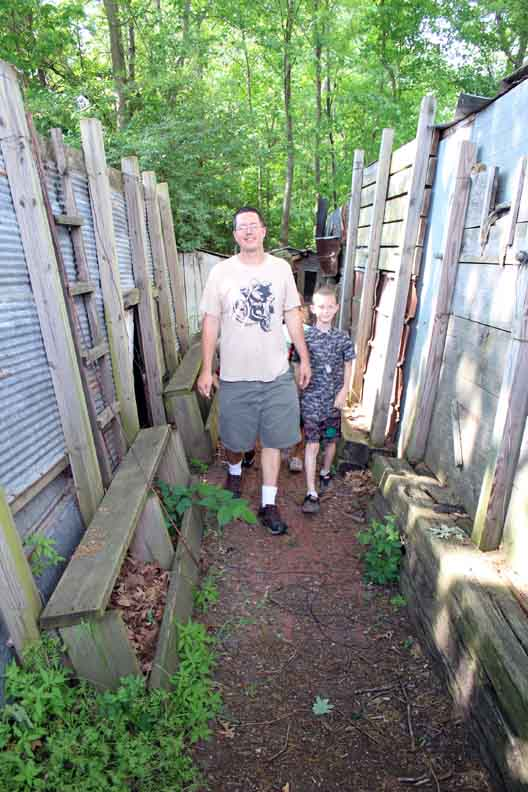 A man and his son walking in the trench.