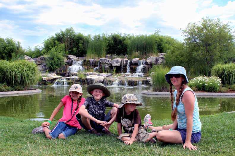 a family in front of a waterfall looking happy having added Tanganyika Wildlife Park to their Wichita Bucket list