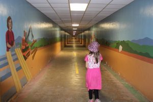 A little girl walking down a tunnel that has murals on the walls.