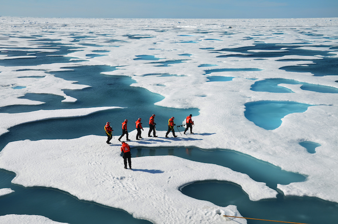 Sea ice researchers, surrounded by Arctic melt ponds, set out to check the thickness of an ice floe. Credit: Don Perovich