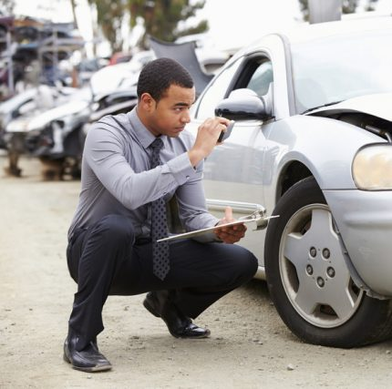 Insurance Adjuster Taking Photograph Of Damage To Car
