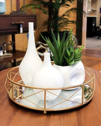 Small glossy white vases complemented with a succulent mix in white dented pot. The tray has golden finish with mirrored base.
