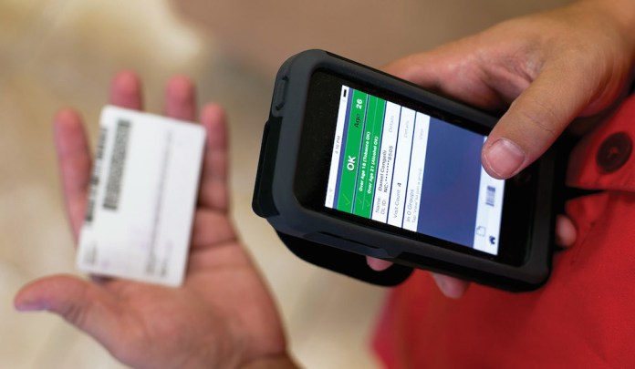 An employee at the North Carolina ABC store in Cameron Village shopping center in Raleigh, N.C. uses the AgeID app to check a drivers license at the checkout resister on Thursday, August 18, 2016.