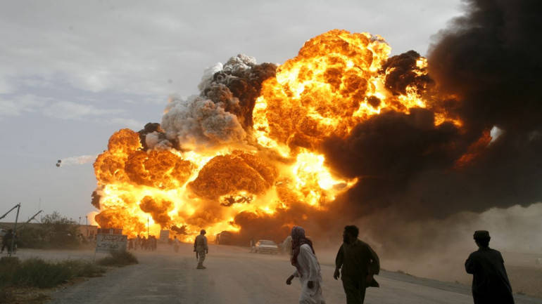 Men run away from burning oil tankers, used to carry fuel for NATO forces in Afghanistan, as they explode
