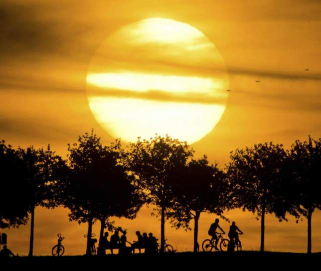 In This Photo People Are Silhouetted Against The Setting Sun While Strolling On The Kronberg Hill