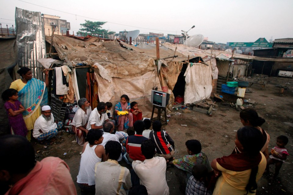 "Group of Indian men and women surrounding tiny box TV to watch ""Slumdog Millionaire"" movie, in the slums."