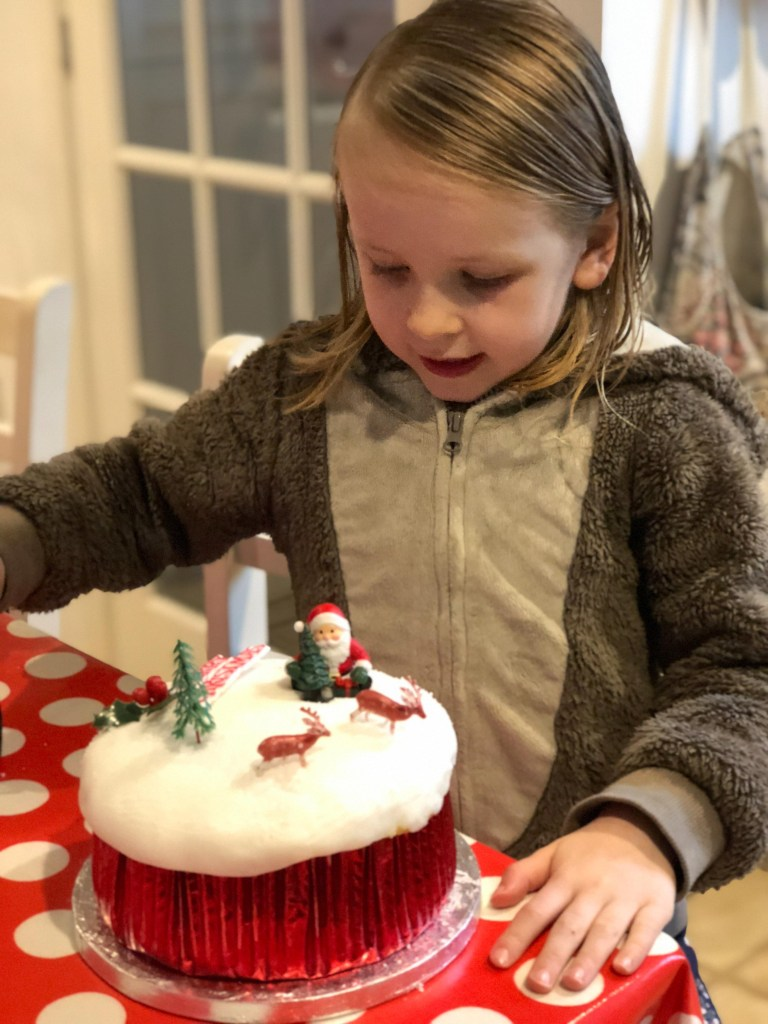 child decorating christmas cakes