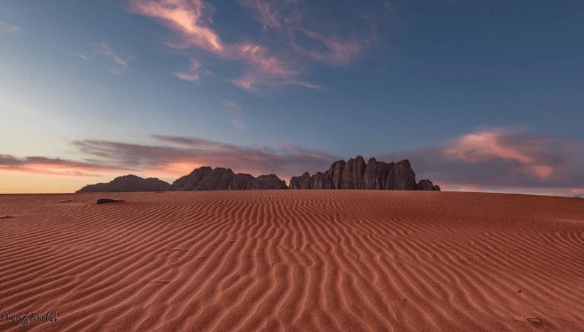 zonsondergang over de rode woestijn met rotsachtige bergformaties in de horizon