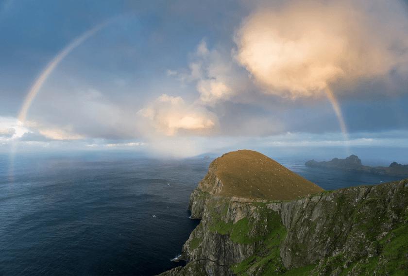 een volle regenboog verschijnt boven de zee aan het einde van een bergklif