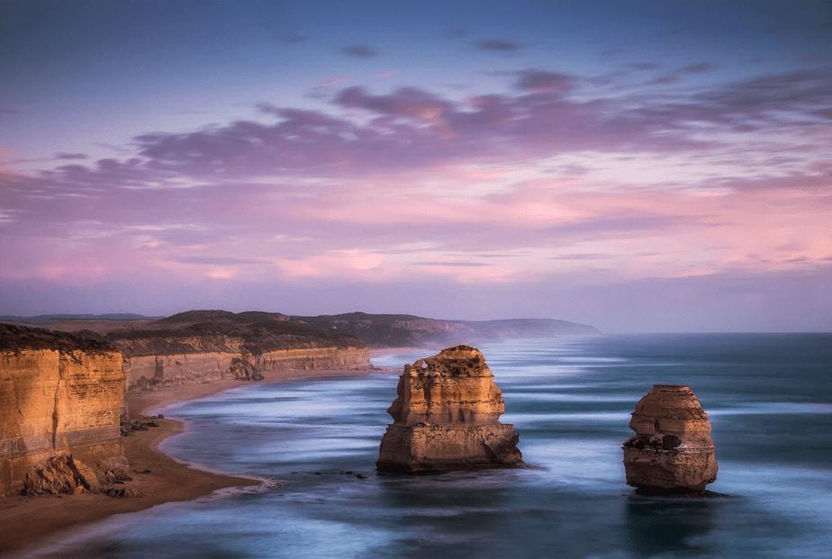 zonsondergang over de zee met klif stranden en rotseilanden