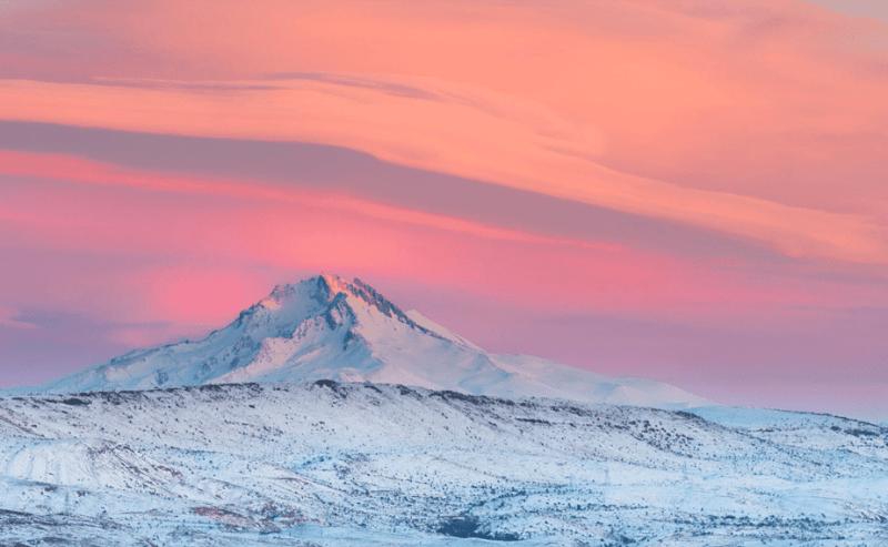 roze en oranje zonsondergang boven een besneeuwde berg