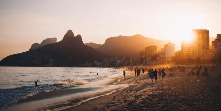 strand zonsondergang met bergen en stad aan de horizon