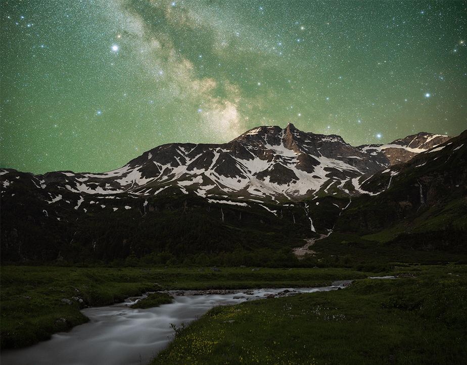 Melkweg over de besneeuwde bergen met een rivier op de voorgrond