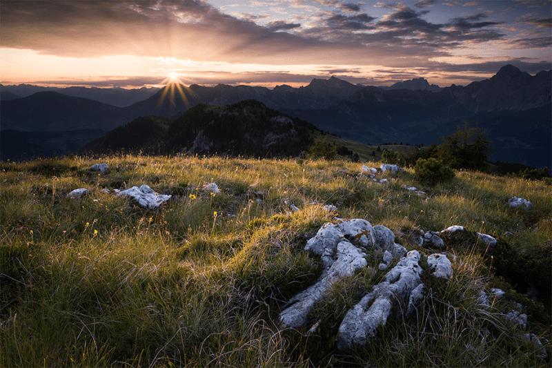 zonsondergang op een bewolkte dag over een groene berg