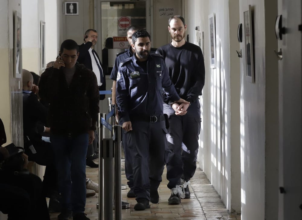 Jonathan Pollak is led to the Jerusalem Magistrate's Court for a hearing, January 15, 2020. (Oren Ziv)