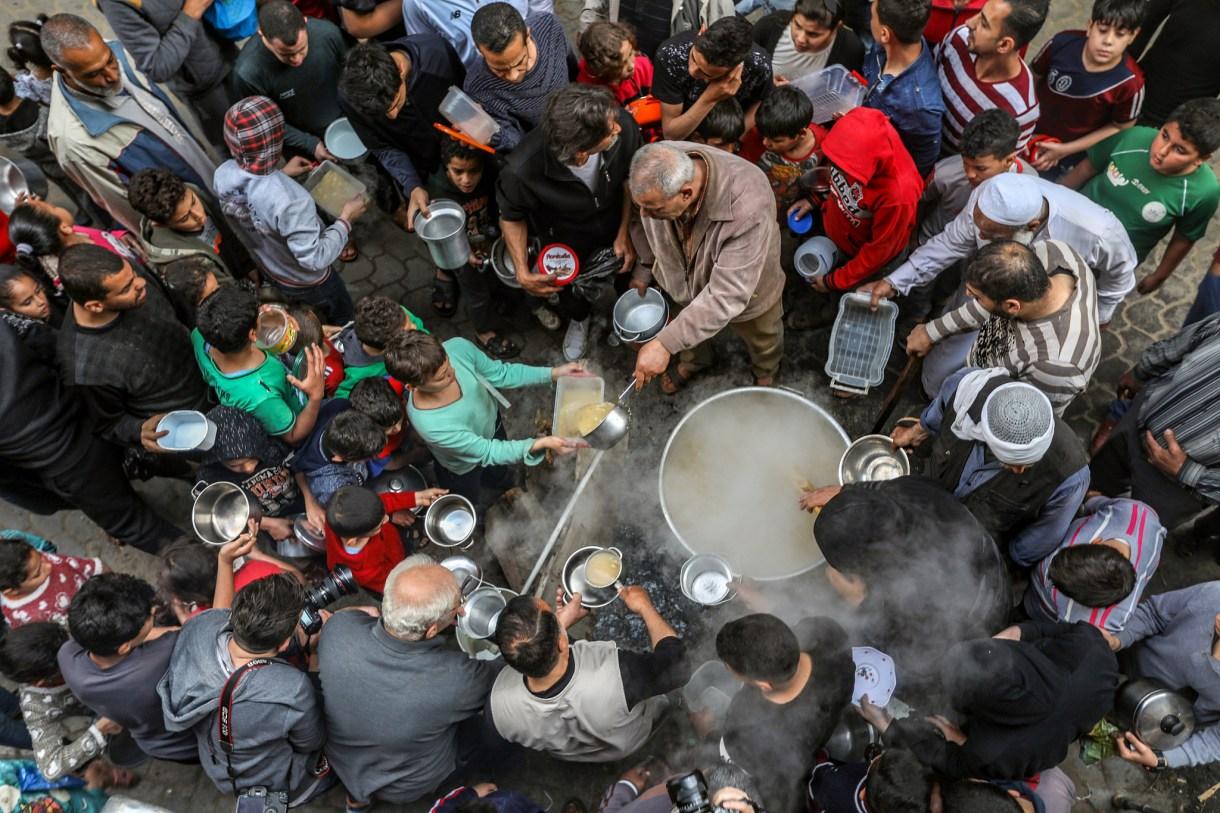 Residents of the Shuja'iyya neighborhood in Gaza huddle around Walid Hattab's cauldron of soup for iftar, April 25, 2020. (Mohammed Zaanoun)