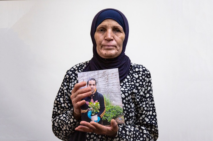 The mother of Iyad Hallak, the Palestinian man with autism who was killed by Border Police officers, holds up a photo of her son, Jerusalem, June 2, 2020. (Activestills.org)