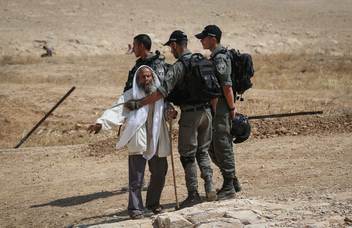 Israeli troops hold back a Palestinian man as they demolish sheds belonging to Palestinians in the South Hebron Hills, June 12, 2019. (Wisam Hashlamoun/Flash90)