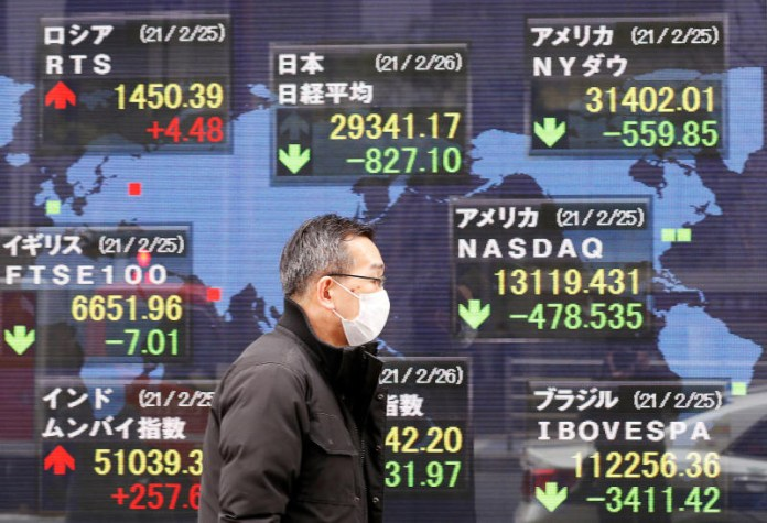 A man walks past a stock quotation board at a brokerage in Tokyo on Feb 26, 2021. (Reuters photo)