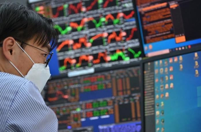 A currency dealer monitors exchange rates in a trading room at KEB Hana Bank in Seoul on Monday. (AFP photo)