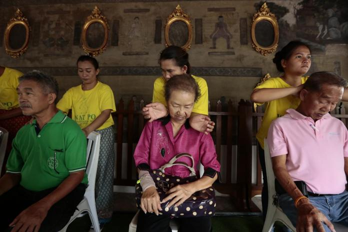 Local tourists get a Thai massage from students at Wat Pho.Patipat Janthong