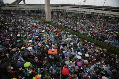 STORM BREWING: Protesters open their umbrellas or wear plastic rain coats to protect them from the rain as they converge at the Lat Phrao intersection. It was one of several protest sites in Bangkok with a heavy turnout on Saturday.