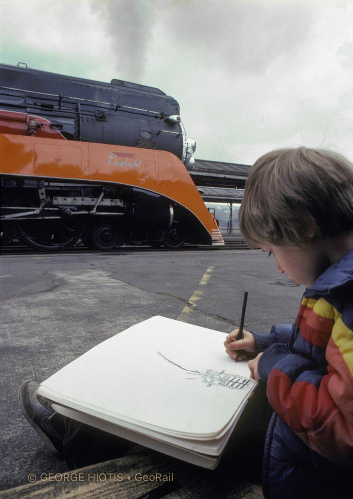 """In Portland, Oregon, a boy draws his favorite subject. He is totally absorbed and doesn't mind the camera. I squeezed behind him with a wide-angle lens to emphasize the foreground. The white paper acts as a fill-light reflector, and the soft light of a cloudy day is ideal for this situation."" Photograph © George Hiotis"