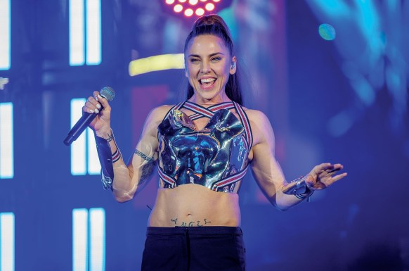 Melanie C smiling at a concert, wearing a blue and red top