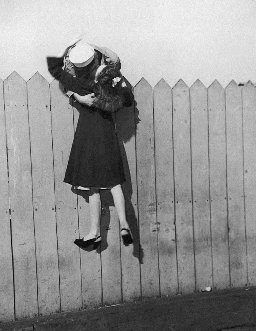 Un marinaio si sporge uno steccato e ascensori sua ragazza in su per un bacio 1945