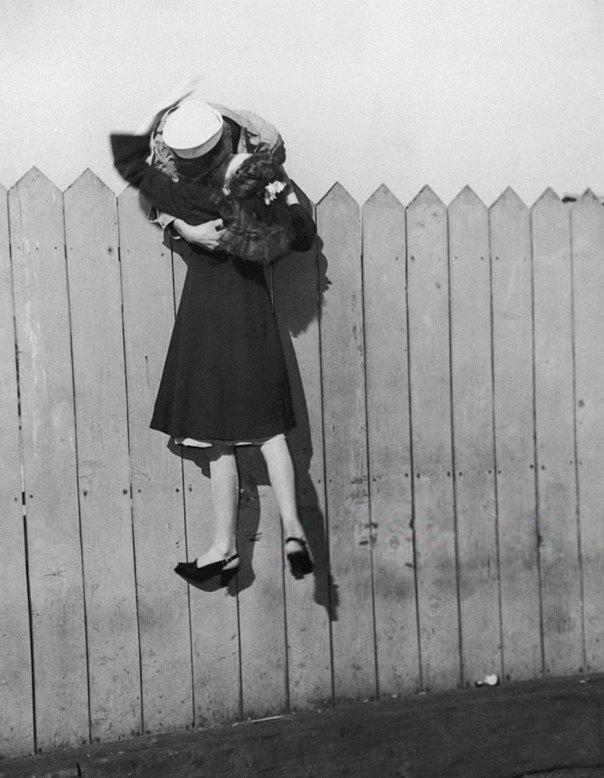 Un marinero se inclina sobre una cerca y elevaciones a su novia para un beso de 1945