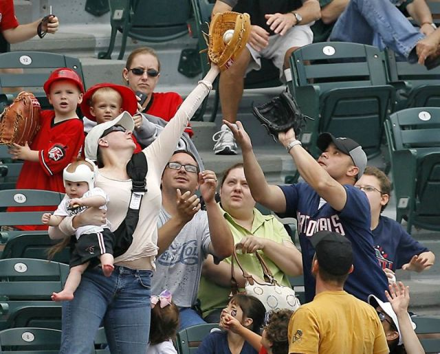 Mom with baby catches a fly ball at a baseball game
