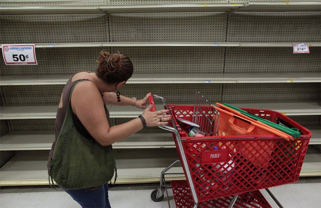 A Woman Looks At Empty Shelves That Are Normally Filled With Bottles Of Water After Puerto Rico Governor Ricardo Rossello Declared A State Of Emergency In San Juan, Puerto Rico