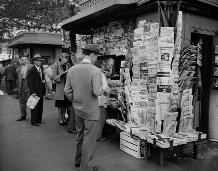 People Browsing Through Magazine Racks At A Busy Sidewalk Newsstand, 1947