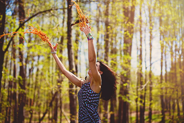 Woman Throwing Spaghetti In A Forest
