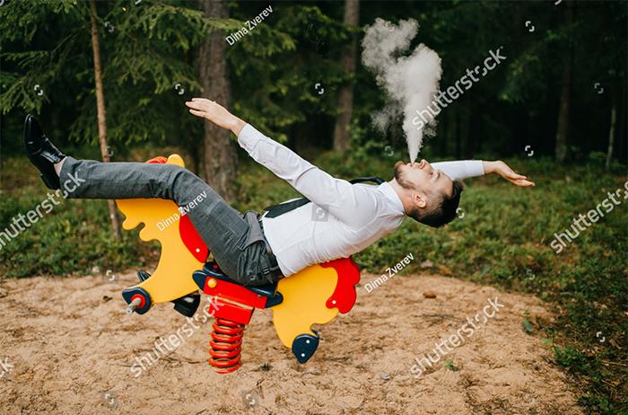 Carefree Man Smoking On A Rocking Horse