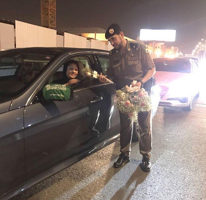 Entrega de oficiales de la policía saudita Out Roses To Women Drivers (Hoy es el primer día que pueden conducir legalmente)