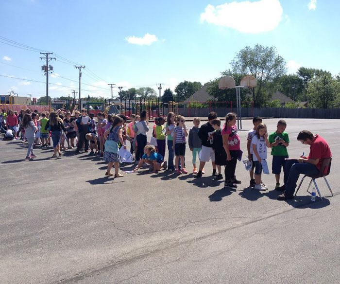 Estudiantes de la escuela primaria se alinean para una firma del anuario de la escuela Conserje