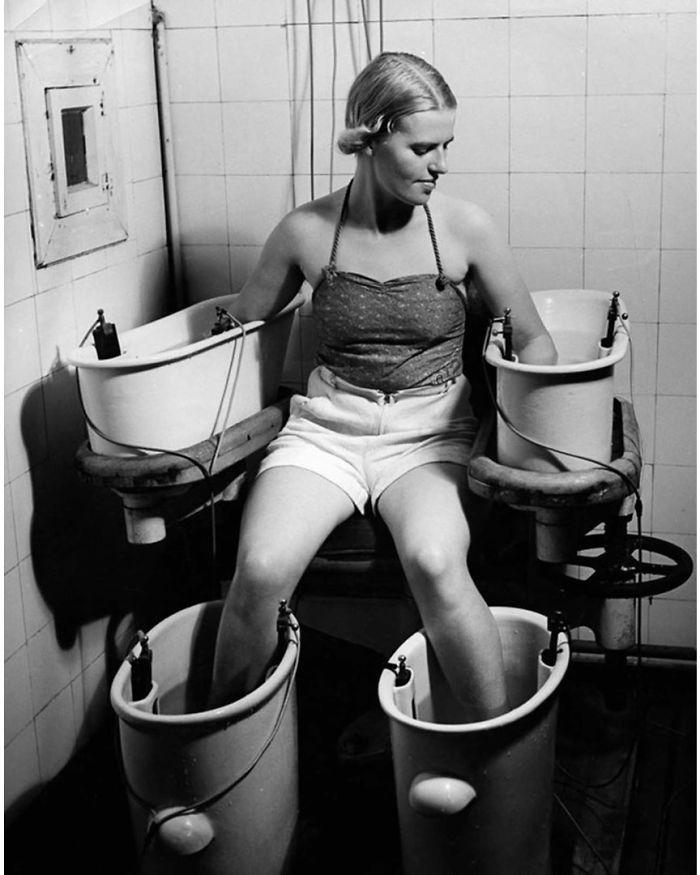 Uma jovem segura os braços e as pernas em quatro banhos de água com corrente elétrica para melhorar a circulação sanguínea, por volta de 1938
