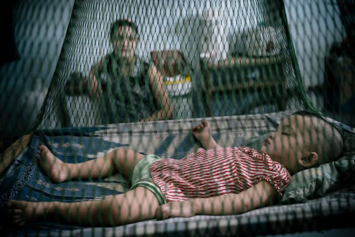 Burmese Migrant And Her Baby Daughter In A Tenement That Houses Burmese Workers In The Thai Fishing Industry