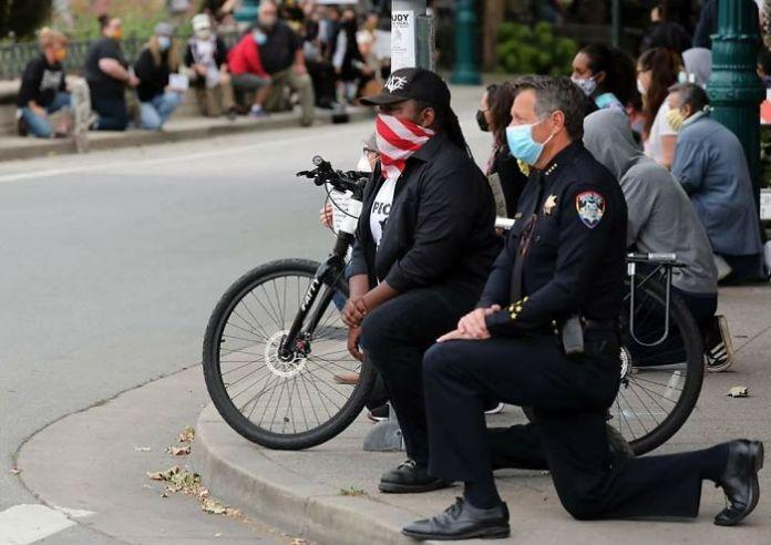 Шеф полиции Санта-Круза принимает колено с мирными демонстрантами во время демонстрации в Санта-Круз, Калифорния