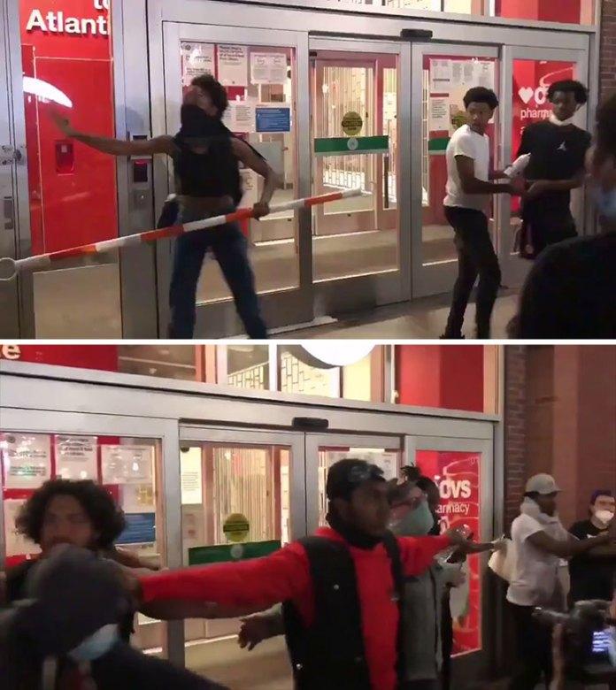 Группа людей, формирующих человеческую баррикаду и защищающих магазин, чтобы предотвратить грабежи людей