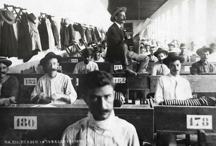A Hired Reader Reads To Cigar Makers Hard At Work In Cuban Cigar Factory (Ca. 1900-1910). Because Many Cigar Factory Employees Were Illiterate Lectors Were Hired To Read Novels, Poetry, Nonfiction Works, And Newspapers Determined By Consensus