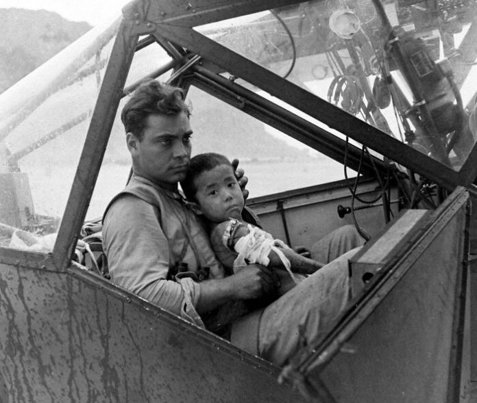 An American Soldier Cradles A Wounded Japanese Boy And Shelters Him From The Rain In The Cockpit Of An Airplane During The Battle Of Saipan While Waiting To Transport The Youngster To A Field Hospital. July, 1944