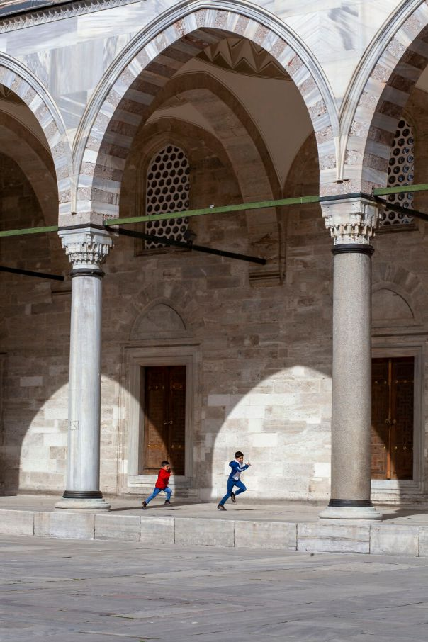 The Pillars Of The Suleymaniye Mosque And The Shadows Of The Arches Create Spectacular Frames Around The Kids Running And Playing Joyfully