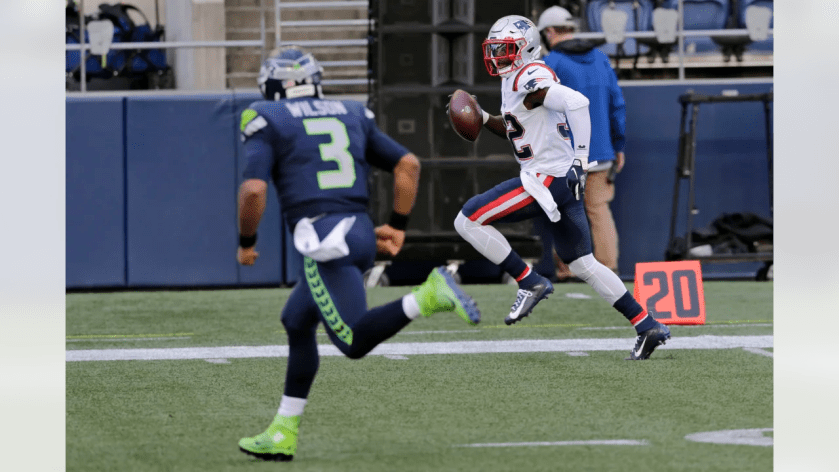 New England Patriots free safety Devin McCourty, right, runs for a touchdown after intercepting a pass from Seattle Seahawks quarterback Russell Wilson (3) during the first half of an NFL football game, Sunday, Sept. 20, 2020, in Seattle. (AP Photo/John Froschauer)