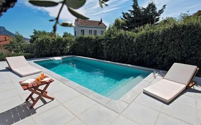 Piscine 6 x 3 rectangulaire, GRI 181, escalier sous liner, margelle classic ton gris, liner gris : à partir de 10 730 euros (*Prix à partir de correspondant à la fourniture d'une piscine, hors pose, hors transport).  Desjoyaux.