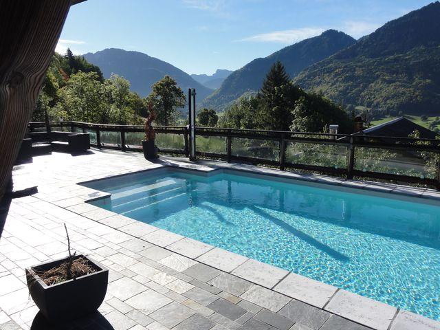 Une piscine en coque de 50 m2 très équipée avec une pompe à chaleur, un volet roulant, une nage à contre-courant et de belles margelles en pierre naturelle (de 20 à 40 000 euros). Génération Piscine.